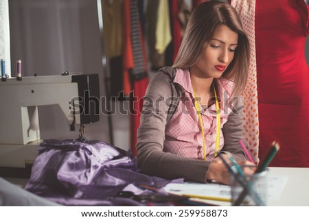 Young fashion designer, with tape measure draped over the neck, drawing sketch for new model. - stock photo