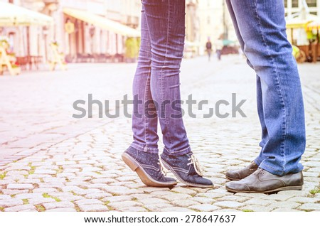 Young fashion elegant stylish couple  feet , in love ,their legs stand opposite each other in old city in spring sunny weather, Vintage sunny colors. - stock photo