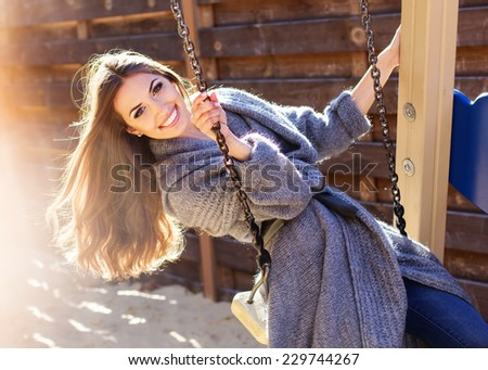 Young fashion girl having fun on swing - stock photo