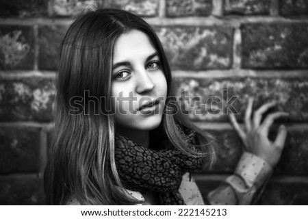 Young fashion girl standing at the brick wall - stock photo