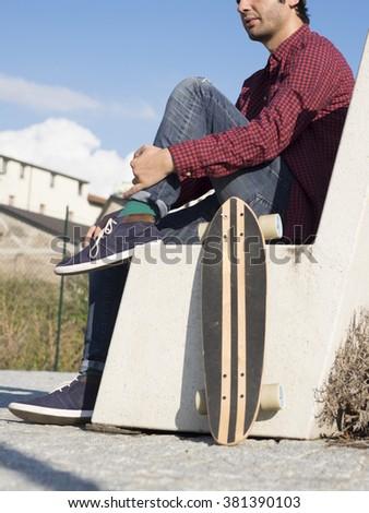 young  fashion guy  vintage lifestyle - skateboard man on retro nostalgic filtered look - stock photo