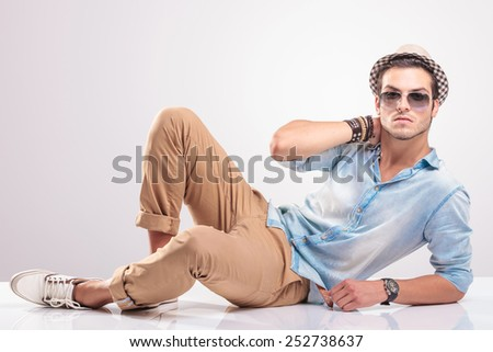 Young fashion man holding his hand to his neck while lying on the floor. - stock photo
