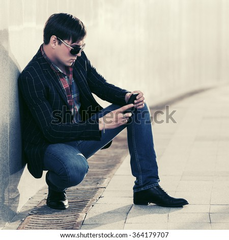 Young fashion man in sunglasses with a mobile phone at the wall - stock photo