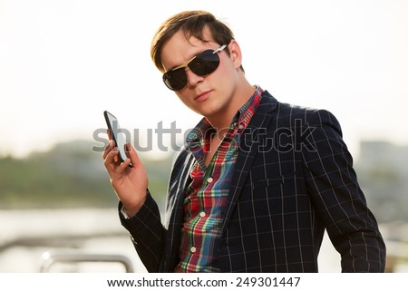 Young fashion man in sunglasses with a mobile phone outdoor - stock photo