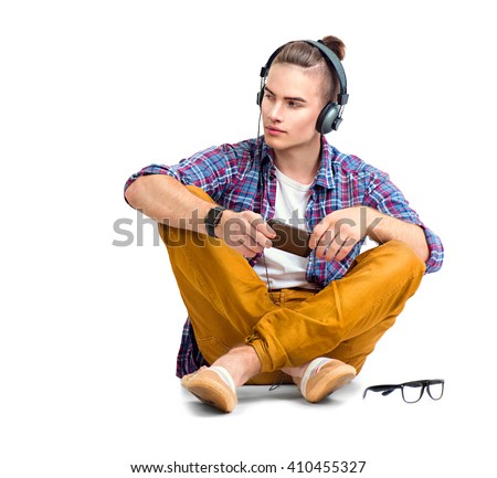 Young fashion man sitting on the floor and enjoying music with his headphones. Handsome young stylish hipster guy in headphones holding smart phone and listening music, isolated on a white background - stock photo