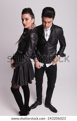 Young fashion man standing beside his girlfriend looking down while she is looking at the camera holding her hands together. - stock photo