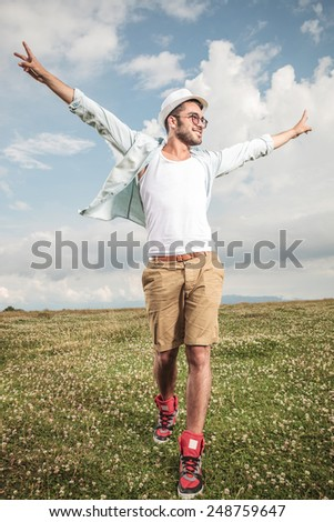 Young fashion man walking on the grass looking away from the camera, holding both hands in the air. - stock photo