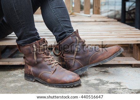 Young fashion man wearing in a  black jeans and brown leather boots on wooden floor. Old leather boots. - stock photo