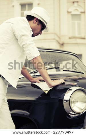 Young fashion man with a road map at the retro car - stock photo