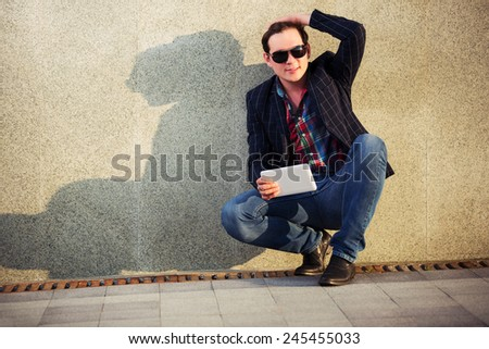 Young fashion man with a tablet computer sitting at the wall - stock photo