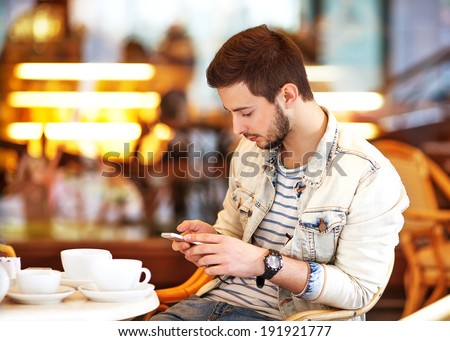 Young fashion man with beard drinking espresso coffee in the city cafe during lunch time - stock photo