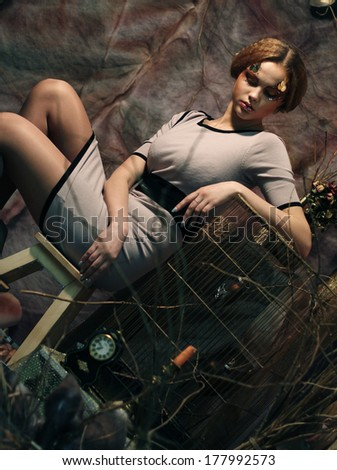 young fashion model sitting on a stool in drama decoration - stock photo