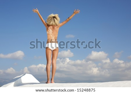 young fashion model wearing golden body make-up posing over sky background with arms outstretched - stock photo