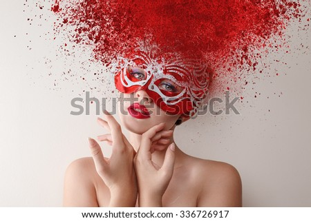 Young fashion model with carnival mask and exploding powder hairstyle - stock photo