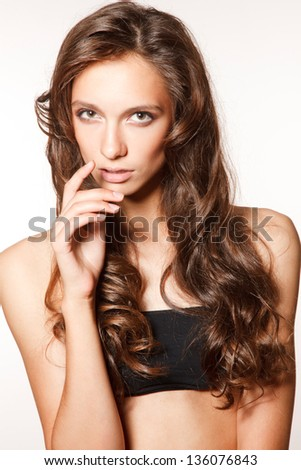 Young fashion sensual woman,dressed in short black top on the white background.Picture is ideal for hair&skin care products commercial - stock photo