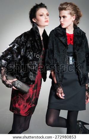 Young fashion two girl wearing elegant black clothes on gray background  - stock photo