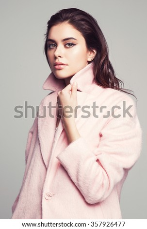 young fashion woman beauty portrait posing in studio wearing in pink coat - stock photo