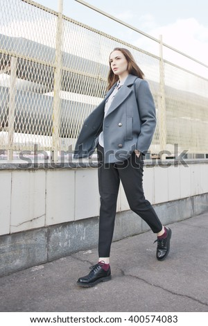 young fashion woman in grey coat walking in street, hands in pockets - stock photo