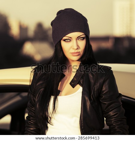 Young fashion woman in leather jacket by her car - stock photo