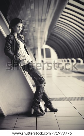 Young fashion woman in modern tunnel. Film style colors. - stock photo