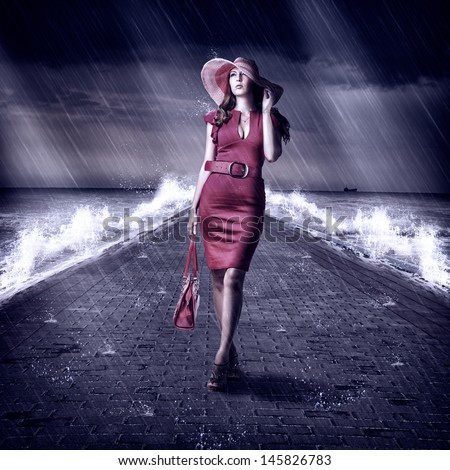 Young fashion woman in red dress and hat is on the Sea pier during a storm and rain holding handbag - stock photo