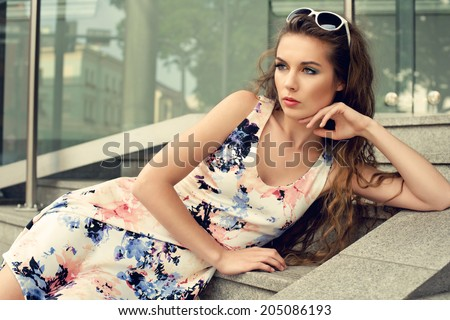 young fashion woman wearing dress posing on stairs - stock photo