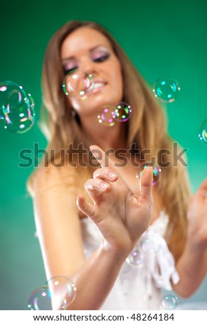 Young fashion woman with soap bubbles. Focus on hand. - stock photo