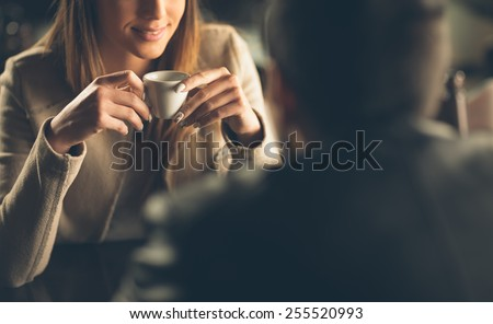 Young fashionable couple dating at the bar, she is having a coffee - stock photo