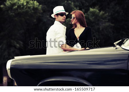 Young fashionable couple in love at the retro car - stock photo