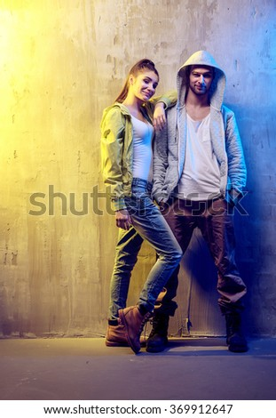 Young fashionable couple on a concrete wall background - stock photo