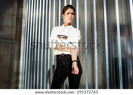 Young fashionable hipster girl in trendy clothing standing on metallic wall background with copy space for your text message or content, fashionable young woman posing outdoors against chrome wall - stock photo