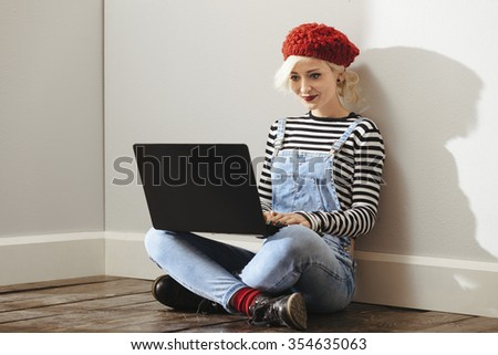 young fashionable lady sitting in an empty room with wooden floor and using her laptop - stock photo
