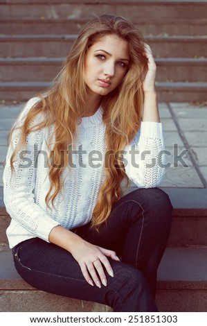 Young fashionable model with long blond hair sitting on the steps. Outdoor shot - stock photo