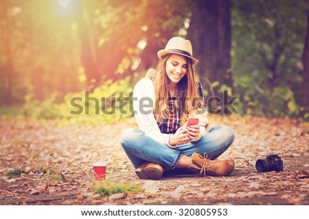 Young fashionable teenage girl with smartphone, camera and takeaway coffee in park in autumn sitting at smiling. Trendy young woman in fall in park texting. Retouched, vibrant colors. - stock photo