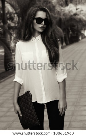Young fashionable trendy girl posing at tropical alley between palms in evening soft light. Vogue style toned portrait of young woman in black jeans, white blouse and sunglasses holding handbag. - stock photo