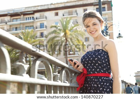 Young fashionable woman holding and using a smartphone to send a message while standing in a city bridge with railings, buildings and street lamps during a sunny day in the summer. - stock photo