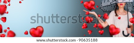 Young fashionable woman holding umbrella standing against grey background red hearts are floating around her. Love rain on Saint Valentine`s Day concept. Copyspace - stock photo