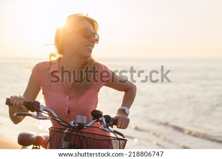 Young fashionable woman riding bicycle on the beach at sunset - stock photo