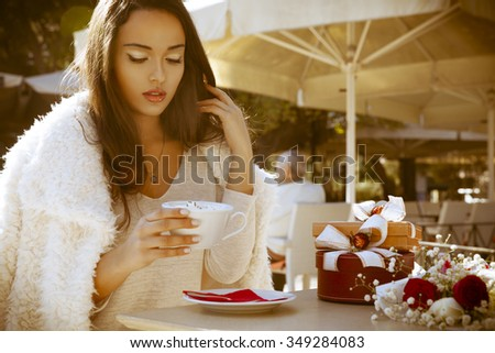 Young fashionable woman sitting in cafe on the street and drinking cappuccino. Table with cappuccino, bouquet of flowers and expensive gifts. Outdoors shot in vintage style. Horizontal - stock photo