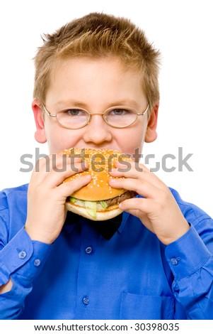 Young fat school boy eating hamburger - stock photo