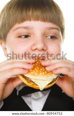 young fat schoolboy eating a big hamburger - stock photo