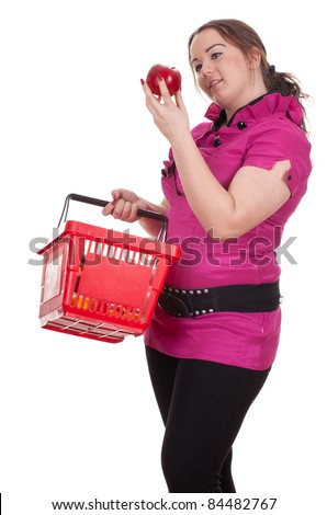 young fat woman with shopping basket keeping red apple - stock photo