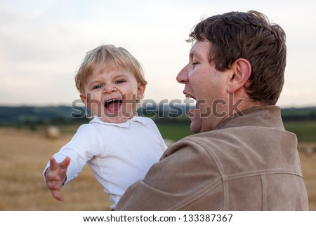 Young father and  adorable little son having fun on straw field, Germany. - stock photo