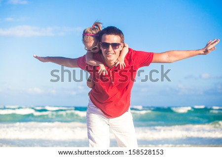 Young father and his adorable little daughter flying like a bird at tropical beach - stock photo