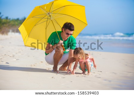 Young father and his adorable little daughter hiding from the sun under a yellow umbrella - stock photo