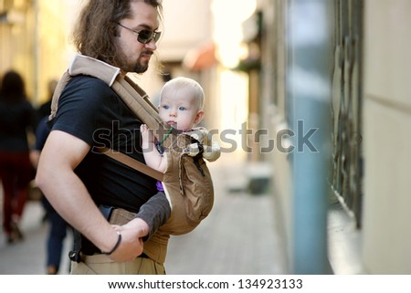 Young father and his baby girl in a baby carrier - stock photo