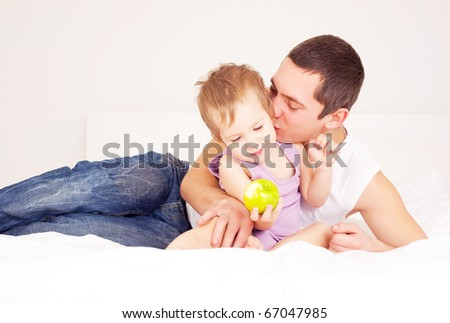 young father and his baby on the bed at home - stock photo