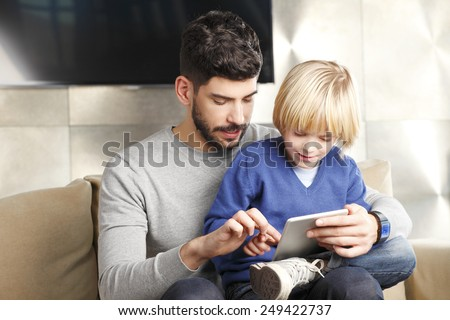 Young father and his cute son playing together on digital tablet. - stock photo