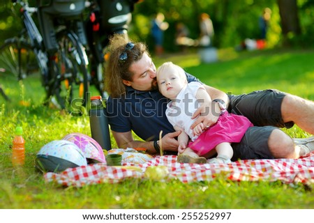Young father and his daughter having a picnic in a park on beautiful summer day - stock photo