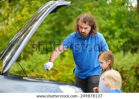 Young father and his daughters checking oil level in a family car - stock photo
